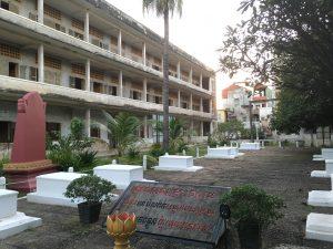 Vue sur le premier des quatre bâtiments et sur les tombes des dernières victimes retrouvées mortes à S21 par les opposants des Khmers Rouges